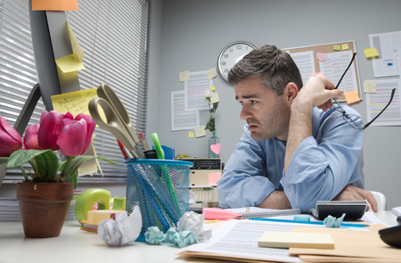 Stressed office man with too much paperwork in dire need of digital transformation