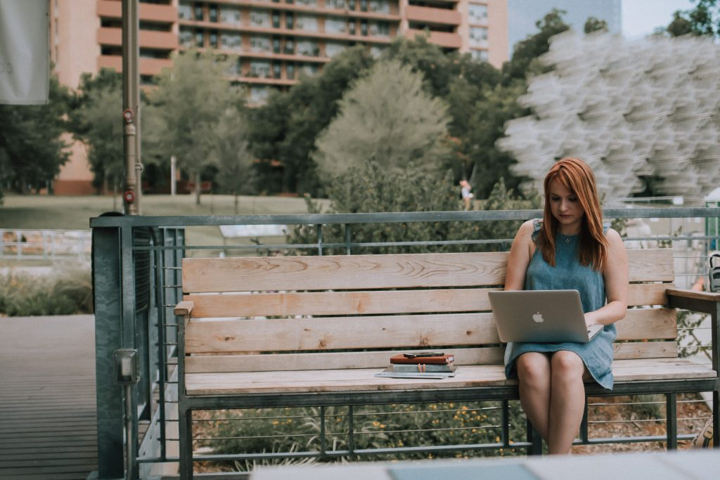 Woman sitting on park bench working on a laptop